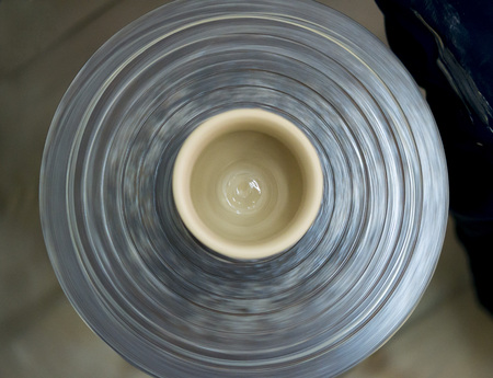 Raw clay jars pots stand and turns potters wheel in the potters workshop close. Art, creativity. Top view Stock Photo