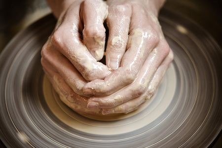 Master potter folded together hands sculpts a clay product on a potters wheel close-up. Hand skin stained with clay and wet Stock Photo