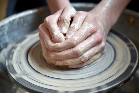 Master potter folded together hands sculpts a clay product on a potters wheel. Hand skin stained with clay and wet