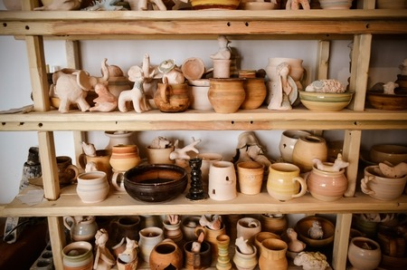makes: Wooden racks in a pottery workshop in which there are pottery, many different pottery standing on the shelves in a potery workshop. Low light Stock Photo