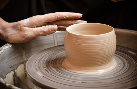 Master class on modeling of clay on a potters wheel In the pottery workshop