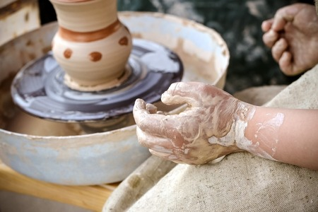 Creating vase of white clay close-up. The sculptor in the workshop makes a jug out of earthenware closeup. Twisted potters wheel. Master crock.