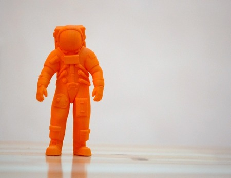 prototyping: The model printed on a 3d printer. The object in the form of an orange cosmonaut is on the table. Progressive modern additive technology. Copy spase, spase for text.