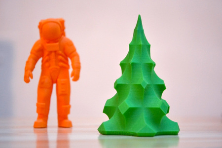 prototyping: The model printed on a 3d printer. The object in the form of an orange cosmonaut and a green Christmas tree stands on a table. Progressive modern additive technology. Copy spase, spase for text. Stock Photo