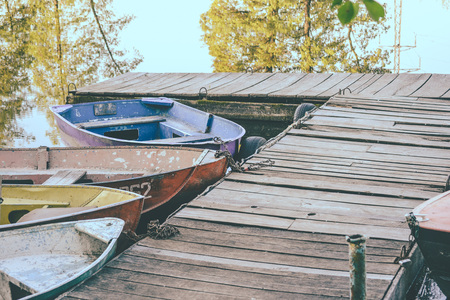 attached: Old iron frayed and shabby boat tied to wooden dock close-up