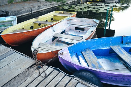 A few old shabby and worn boats different colors on the dock pier close-up