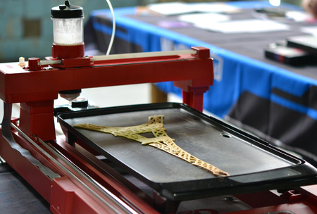prototyping: 3d printer for liquid test. 3D printer printing pancakes with liquid dough different shapes close-up. Stock Photo