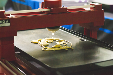 technic: 3d printer for liquid test. 3D printer printing pancakes with liquid dough different shapes close-up. Stock Photo