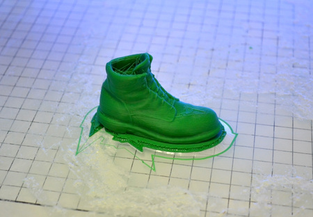 3D printer prints the form of plastic green close-up. Automatic three dimensional 3d printer performs plastic modeling in laboratory. Progressive modern additive technology