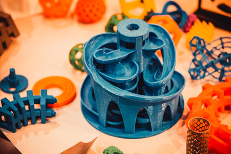 Models printed by 3d printer. Copy space. Bright colorful objects printed on a 3d printer on a table. Modern additive technologies 4.0 industrial revolution Stock Photo