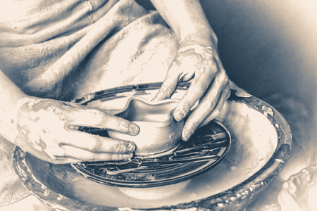 craftswoman: person potter makes clay earthen pot on a potters wheel in pottery workshop