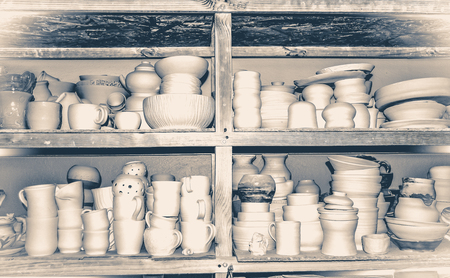 not painted: Bright pottery. Many white, not painted clay pottery standing on wooden shelves