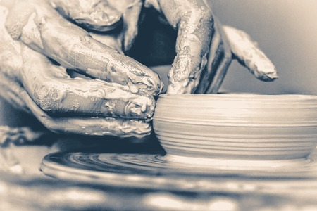 makes: Macro the potter makes earthen pot, hands doing clay plate. Old vintage style. Stock Photo