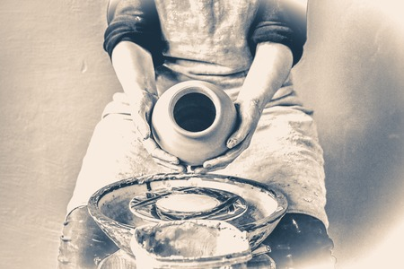 Potter holds more crude to the firing of white clay jug. Sculptor sculpts pots products from white clay. Master keeps on empty hands open earthen vessel. Workshop pottery. Old vintage style.
