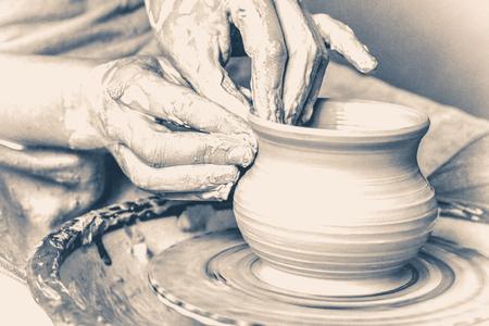 antique vase: potter making vase from clay. Hands close-up master. Old vintage style.