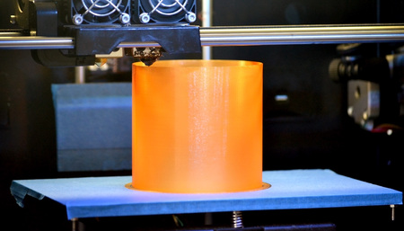 3D printer prints the form of molten plastic orange close-up. Automatic three dimensional 3d printer performs plastic modeling in laboratory. Progressive modern additive technology Stok Fotoğraf