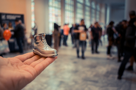 printed material: Object in the form of a boot printed on a 3d printer and covered with enamel on hand close-up. On the back of a blurry plan - people. Progressive modern additive technology. Copy spase