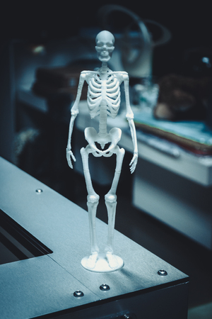 object human skeleton printed by 3d printer. Automatic three dimensional 3d printer performs plastic green colors modeling in laboratory. Modern 3D printing technology.