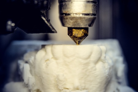 customizable: 3D printer prints the form of molten plastic white close-up. Automatic three dimensional 3d printer performs plastic modeling in laboratory. Progressive modern additive technology