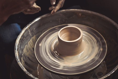 Creating vase of white clay close-up. Master crock.The sculptor in the workshop makes a jug out of earthenware closeup. Twisted potters wheel. Man hands making clay jug macro. Stock Photo