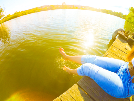 girl in blue jeans sits on the old wharf in the lake on a sunny day. Caucasian. Stock Photo