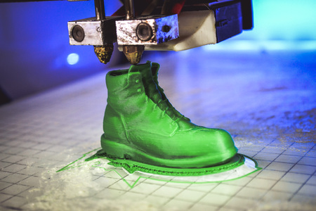 prototyping: 3D printer prints the form of molten plastic green close-up. Automatic three dimensional 3d printer performs plastic modeling in laboratory. Progressive modern additive technology