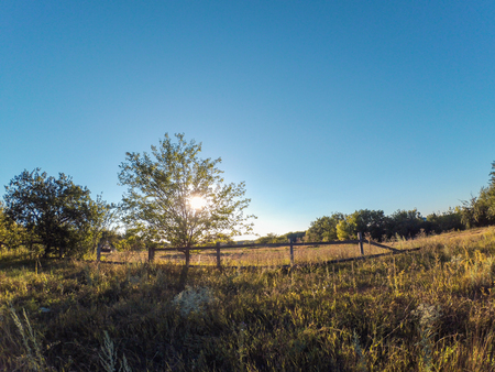 Landscape field fence setting sun summer. Natural background. Copy space.