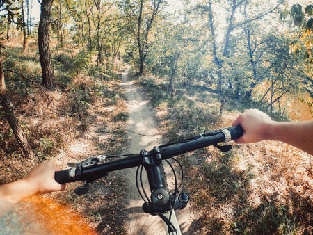 Bicycle steering wheel hand path forest trees green go pro action camera. Copy space. 版權商用圖片