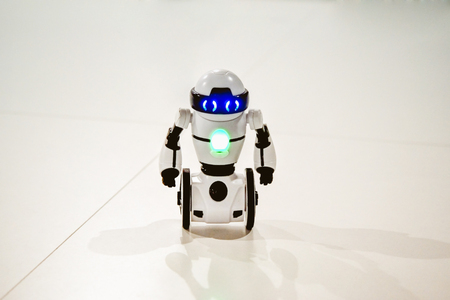 Small robots, humanoid with small wheels instead of legs and luminous eyes close-up. Artificial Intelligence. AI. Smart robot. Concept of 4.0 industrial revolution