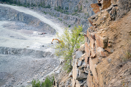 The walls of the granite quarry in summer day. Copy sapce.