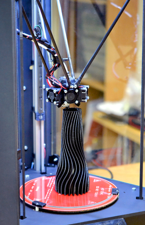 A black vase made on a 3d printer stands on the work surface close-up. Progressive modern additive technologies 4.0 industrial revolution