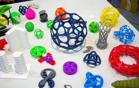 Abstract models printed by 3d printer close-up. Bright colorful objects printed on a 3d printer on a white table. Progressive modern additive technology. Concept of 4.0 industrial revolution