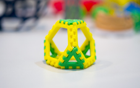 deposition: Abstract object of a yellow green color printed on a 3d printer on a white table. Fused deposition modeling, FDM. Progressive modern additive technology. Concept of 4.0 industrial revolution