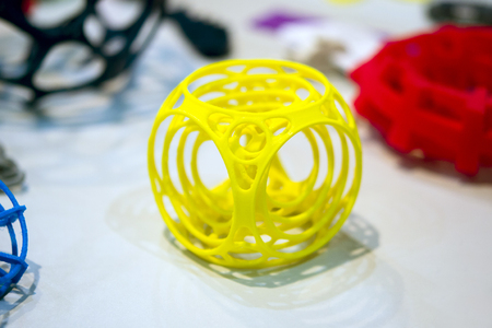 deposition: Abstract object of a yellow color printed on a 3d printer on a white table. Fused deposition modeling, FDM. Progressive modern additive technology. Concept of 4.0 industrial revolution