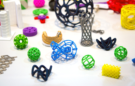 deposition: Many abstract models bright colorful objects printed on a 3d printer on a white table. Fused deposition modeling, FDM. Progressive modern additive technology. Concept of 4.0 industrial revolution Stock Photo