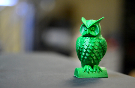 The green form in the form of a small owl created on a 3d printer stands on the surface of a dark blurry background close-up. Stockfoto