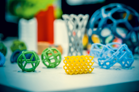 Many abstract models bright colorful objects printed on a 3d printer on a white table. Fused deposition modeling, FDM. Progressive modern additive technology. Concept of 4.0 industrial revolution Stock Photo