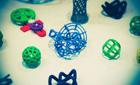 Many abstract models bright colorful objects printed on a 3d printer on a white table. Imagens
