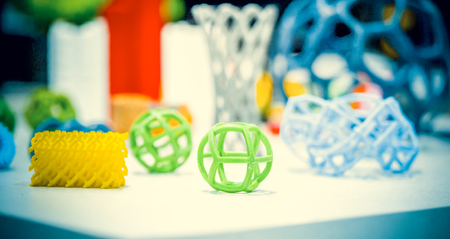 Abstract models printed by 3d printer close-up. Bright colorful objects printed on a 3d printer on a white table.