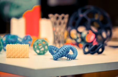 Many abstract models bright colorful objects printed on a 3d printer on a white table. Stock Photo