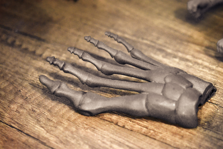 Gray prototype of the human foot skeleton printed on 3d printer on dark surface. Fused deposition modeling, FDM. Progressive modern additive technology. Concept of 4.0 industrial revolution