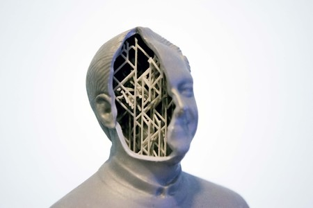 Example of printing a 3d object in the form of a human head with supports isolated on white background. Stereolithography 3D printer, photopolymerization UV light. Additive technology.