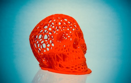 Skull printed with plastic of red color on a 3d printer on blue background