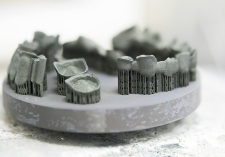 Object printed on metal 3d printer after heat treatment synterization close-up. Dental crowns created in laser sintering machine close-up. DMLS, SLM, SLS technology. Concept 4.0 industrial revolution. Zdjęcie Seryjne