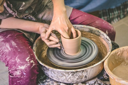 Creating ceramic products of white clay close-up. The sculptor in workshop makes clay jug closeup. Master crock. Twisted potters wheel. Art creativity Cultural tradition Handmade Craft Masters Hands Stock Photo