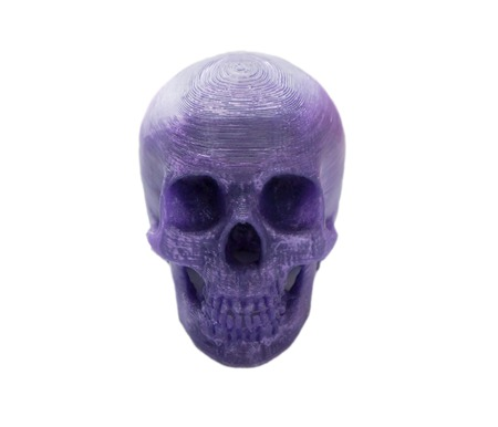 Bright purple object in shape of human skull toy printed on 3d printer isolated on white background. Fused deposition modeling, FDM. Concept modern progressive additive technology for 3d printing Imagens