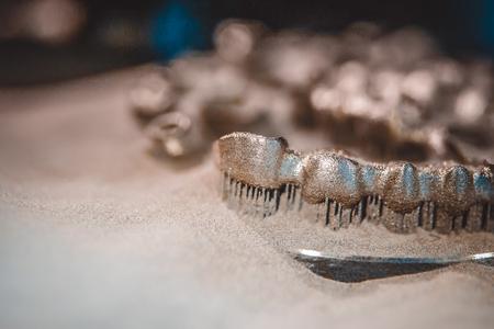 Object printed on metal 3d printer, laser sintering machine for metal close-up. Metal dental crowns sprinkled with metal powder after raising the platform in working chamber. DMLS, SLM, SLS technology