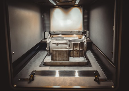 A model with supports created in a laser sintering machine stays in the working chamber. DMLS, SLM, SLS technology. Concept of 4.0 industrial revolution. Progressive modern additive technology.