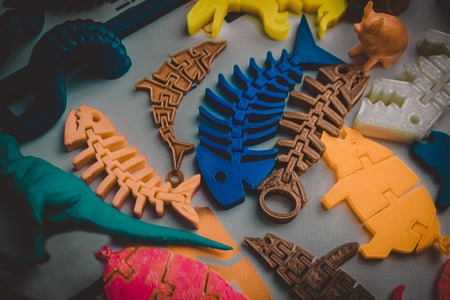 Models printed by 3d printer. Bright colorful objects printed on a 3d printer on a table close-up. Fused deposition modeling, FDM. Concept modern progressive additive technology for 3d printing.