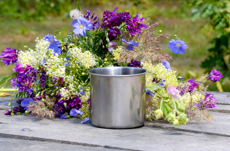 metal mug stands on wooden table beside her lay a bouquet of wildflowers